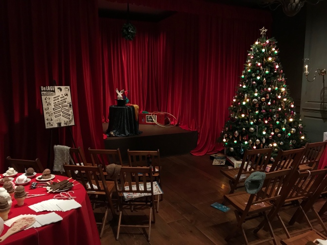 Christmas tree to the left of a stage. Two rows of wooden chairs are for the audience.