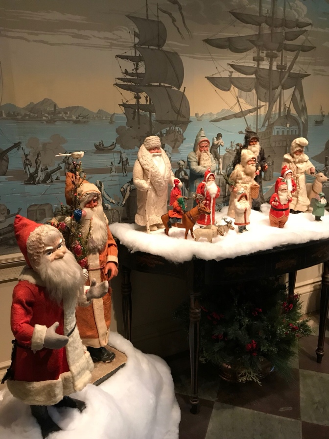 Figurines of Santa Claus and Grandfather Frost. Wallpaper featuring naval sailing ships are on the walls in the background.
