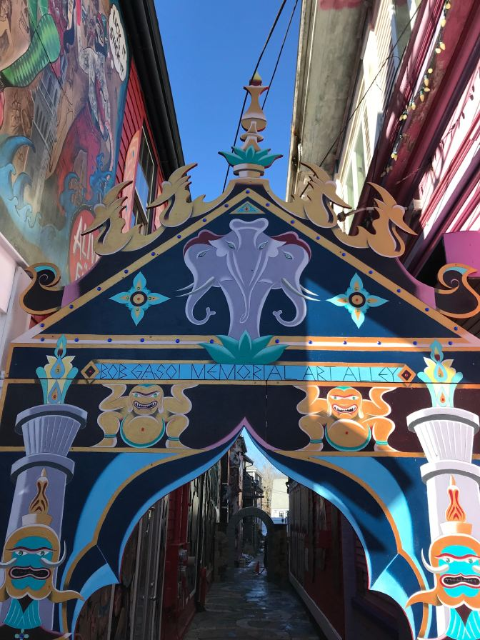 "Decorated arch entrance to an alley. The arch says ""Babydoll Gasoi Memorial Art Alley."""