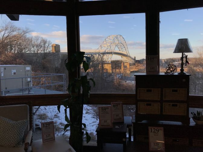 View of the Bourne Bridge from the interior of the store, looking through a window.