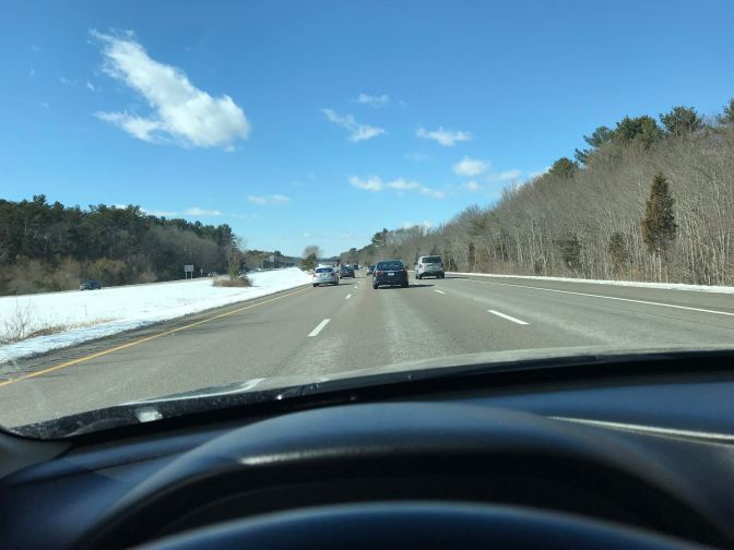 View from behind the wheel of a car on a highway. The sky is blue with a few clouds.