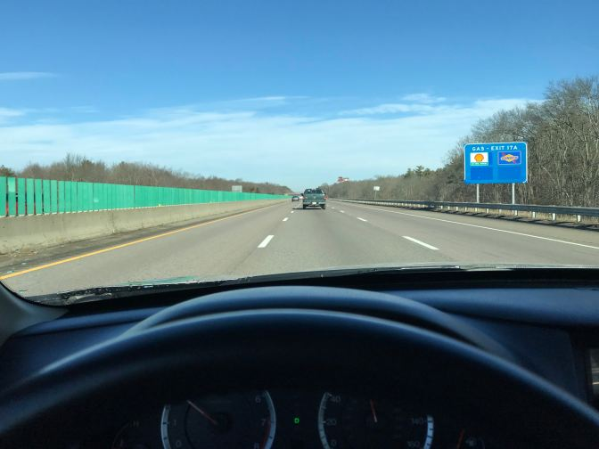 View of highway from behind wheel of car.