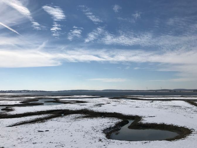 Frozen salt marshes, with clouds in the sky.