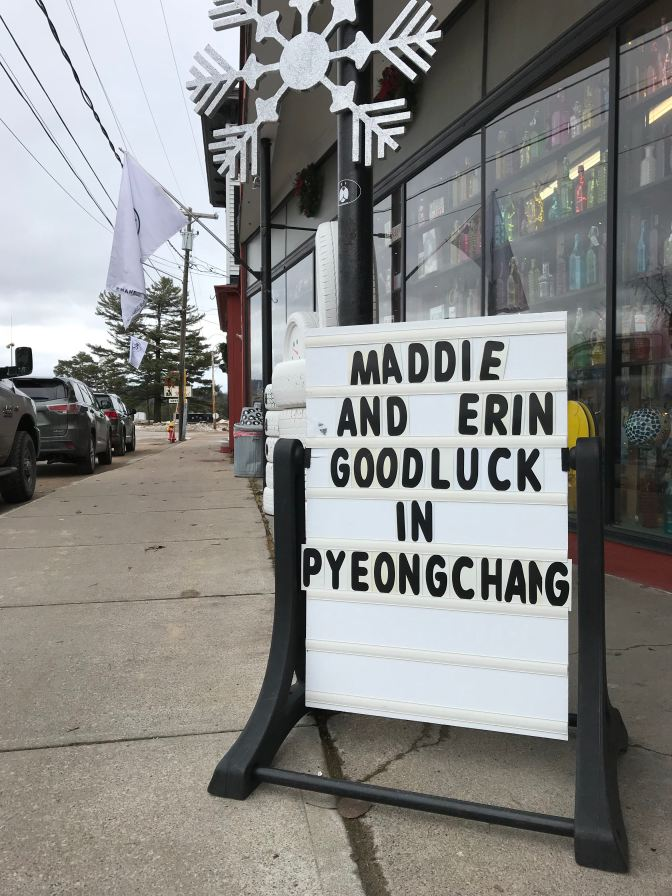 "Sign outside of hardware store that says ""Maddie and Erin Goodluck in Pyeongchang."""