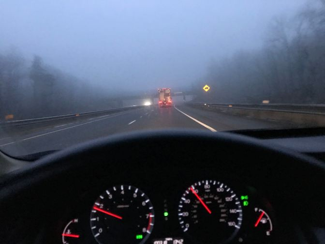 Foggy road at night, with a tractor trailer in the distance. A car's dashboard is in the foreground.