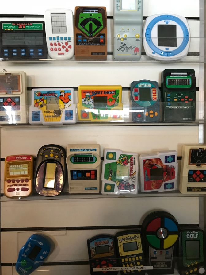 Wall shelves full of electronic games from the 1980s and 1990s.