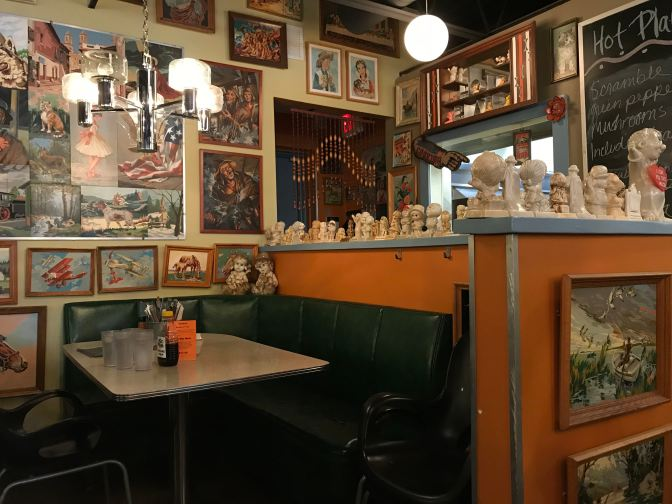 Diner booth, with small porcelain dolls on the shelves behind the table. Paintings adorn the walls.