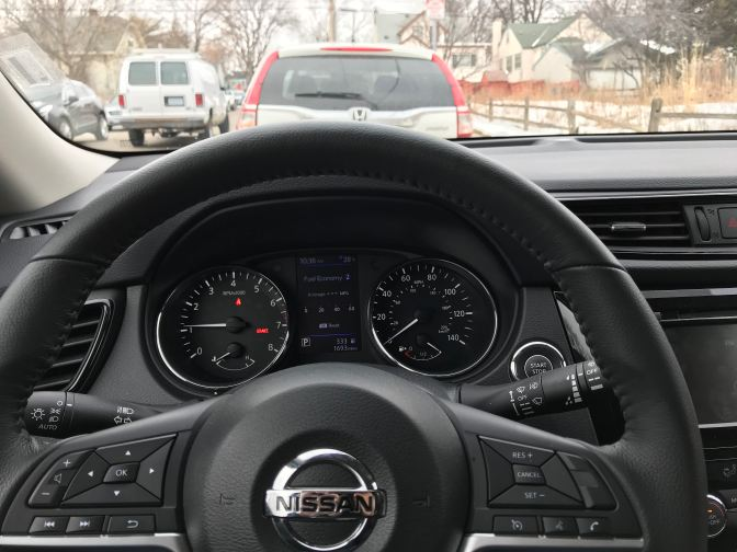 View of steering wheel and dashboard of Nissan Rogue.