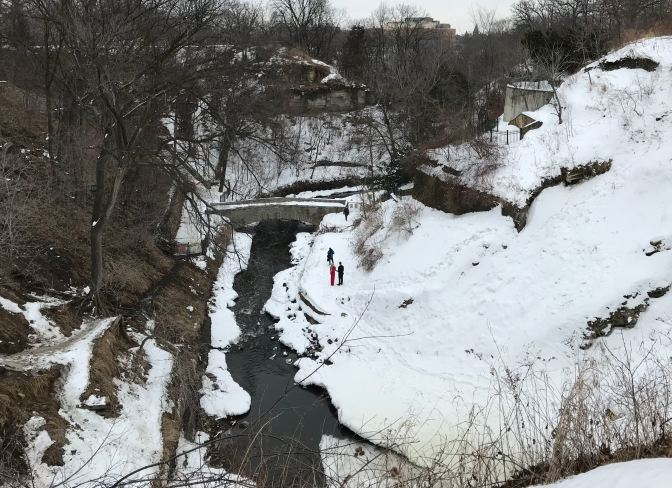 View of the creek, with the surrounding hillsides covered in snow. A couple is having their photographs taken by a photographer on the banks of the Creek.