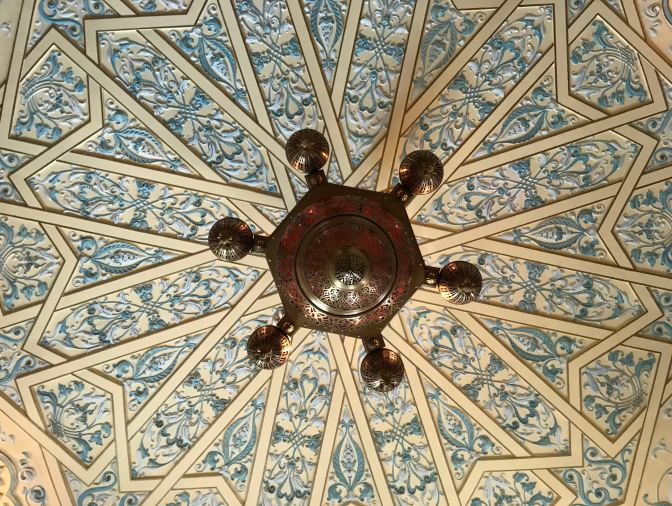 Lattice work ceiling, with chandelier in middle of photo.