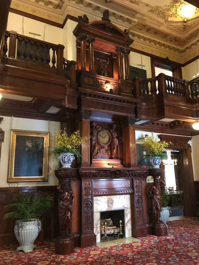 Elaborate wood and marble fireplace in center of living room of mansion.