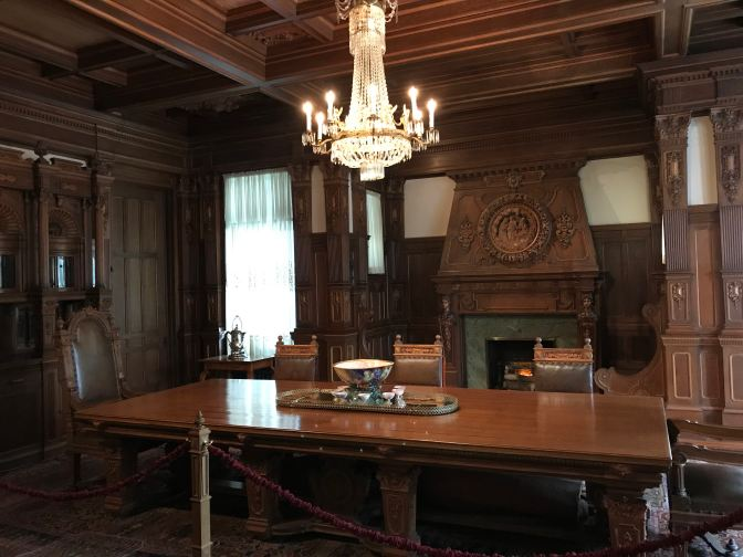 Dining room, with large wood table in the center, and a chandelier hanging above the table. A fireplace is in the background.