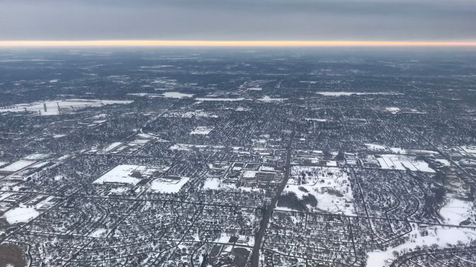 Sunrise on a cloudy day. View is from an airplane window, with the suburbs of Minneapolis in the foreground.