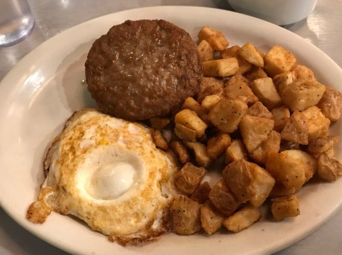 Plate of sausage and egg biscuit, with home fries.