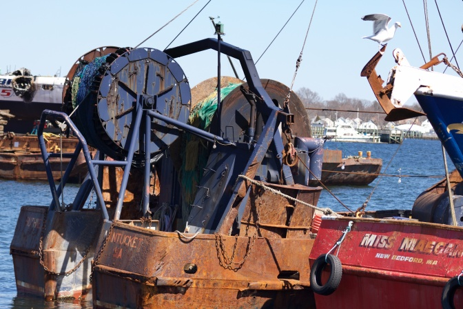 Stern of fishing boats. Boat in center of frame is heavily rusted.