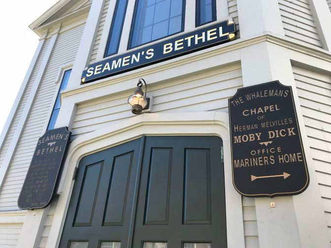 "Signs outside Seamen's Bethel that state ""The Whaleman's Chapel of Herman Melville Moby Dick Office Mariners Home"" and ""Seamen's Bethe."""