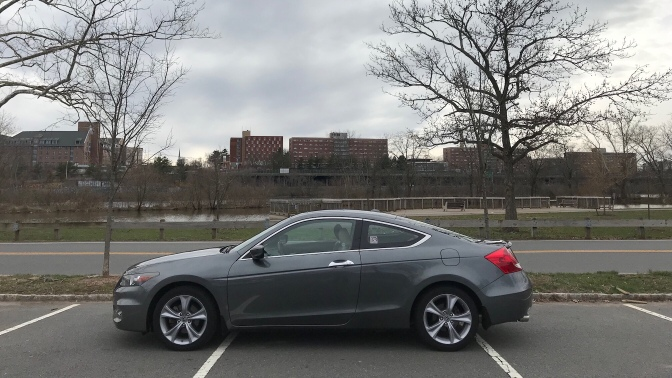 2012 Honda Accord, in front of a river and buildings.