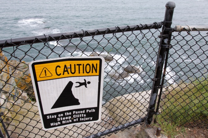"Sign that states ""Caution: Stay on the Paved Path Steep Cliffs High Risk of Injury"" with image of person falling off cliff. The water is behind the image."