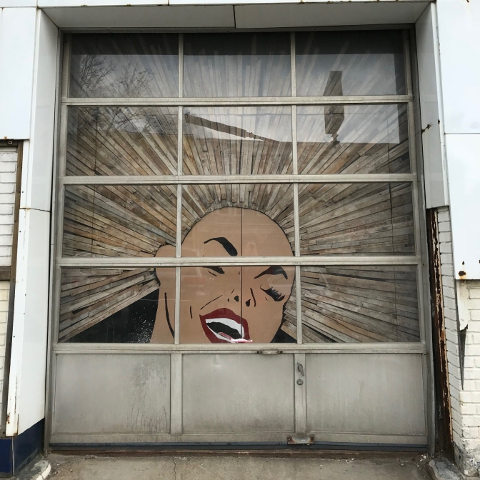 Garage door with painting of woman's face and hair made of wood extending in all directions.