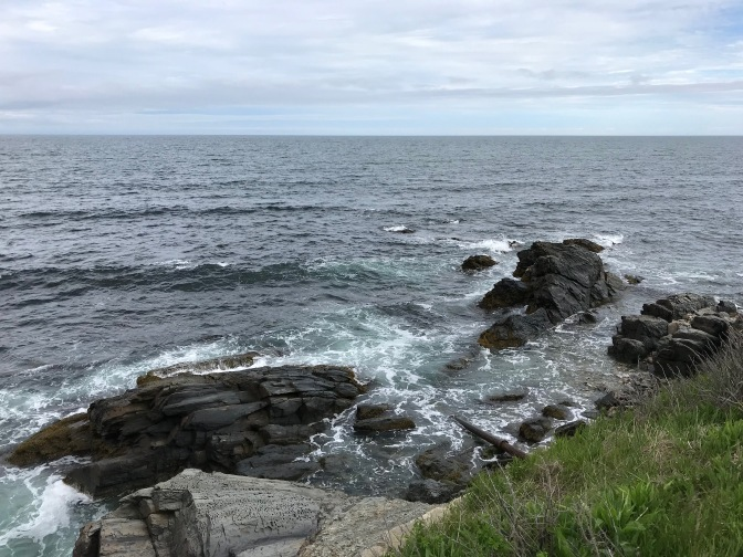 Rocky shoreline, with rock formations in the water beyond the edge of the cliff.