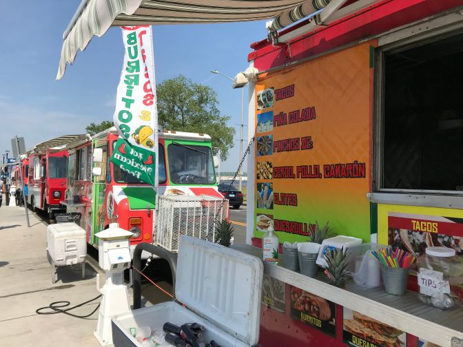 Food trucks at Food truck Paradise. The truck nearest to the camera has a menu of Mexican food items on its side.