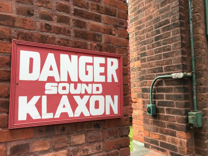 Sign that reads DANGER SOUND KLAXON on a brick wall.