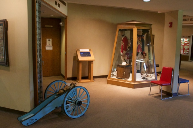 Washington Crossing State Park visitor's center. A small cannon is on the floor in the foreground. In the background is a display with various soldier's uniforms.