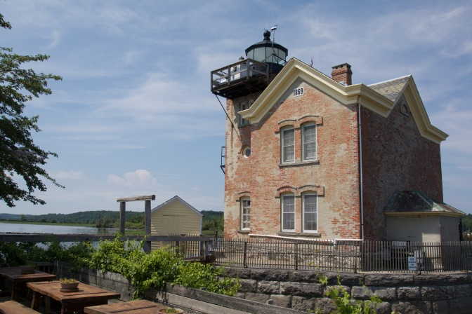 Rear view of the lighthouse. Picnic tables and a small garden is in the foreground.