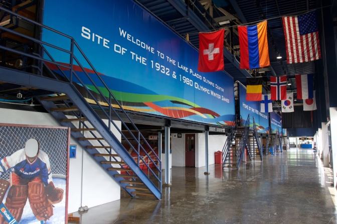 Flags hanging outside the arena, with a sign that says Welcome to the Lake Placid Olympic Center Site of the 1932 & 1980 Olympic Winter Games.