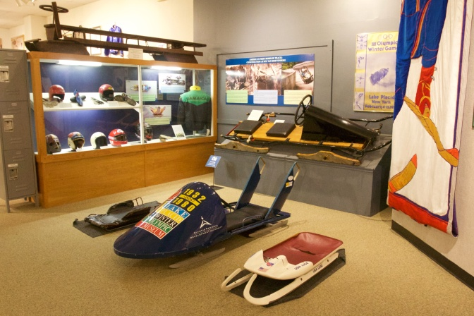 Interior of the Lake Placid Olympic Museum. A skeleton, luge, and bobsled are on the floor. A cutaway of a wooden bobsled is on the wall, along with a display case of bobsled gear including helmets and jackets.