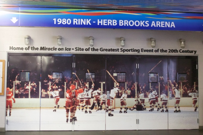 Doors to the Herb Brooks Arena, with a wall-size photo of the US team celebrating its win on the entrance doors.