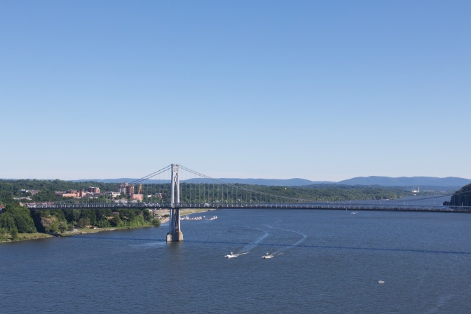 View of the Mid-Hudson Bridge, with boats in the water below the bridge.