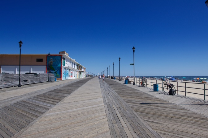 View of the boardwalk, facing north. A building covered in murals is on the left.