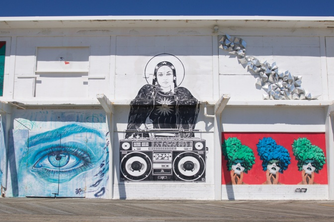 Murals on white wall including an eye in a blue face, three women wearing hats of flowers, and a woman, holding a raven and a boombox.