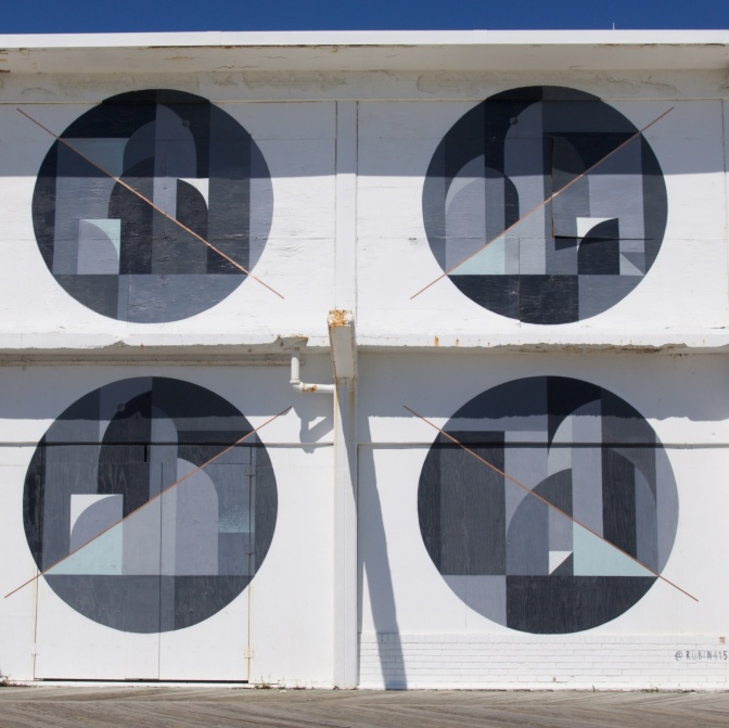 Four circles, arranged in a box formation, with shapes within them on the walls of the building.
