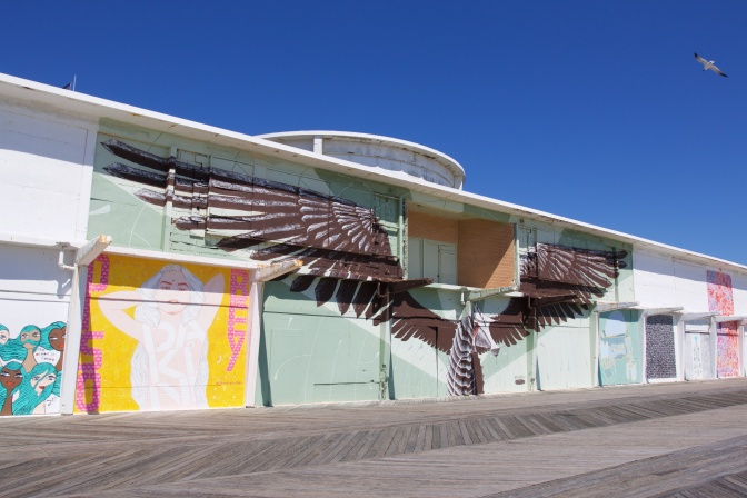 Abandoned Building covered in murals. A large mural of a bird with its wings spread dominates the building.