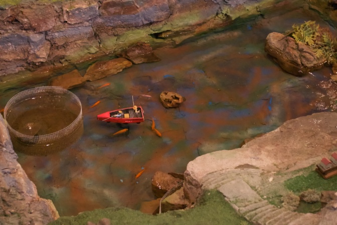 Miniature fishing pond with two model figures inside a model rowboat. Live fish swim in the water.