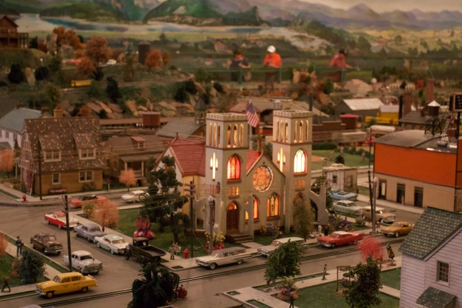Miniature church, surrounded by cars parked on the street.