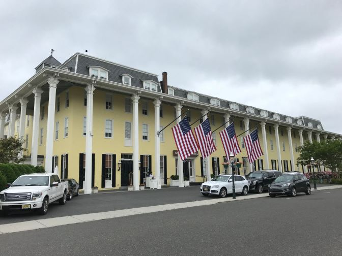 Exterior view of Congress Hall in Cape May, NJ. Vehicles are parked in front of the building.