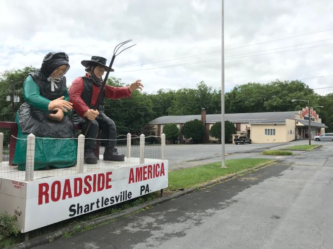 Statues of Amish man and woman seated on a plinth, waving at the traffic.