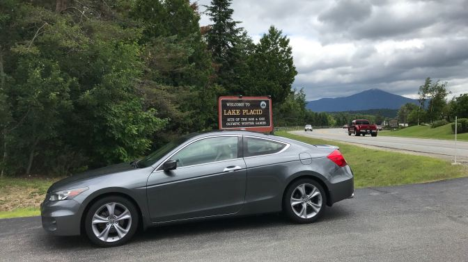 2012 Honda Accord in front of sign that says WELCOME TO LAKE PLACID - Site of the 1932 and 1980 Olympic Winter Games.