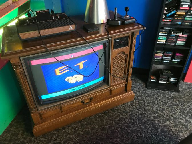 Atari 2600 on top of a vintage television. The game E.T. is displayed on the screen.