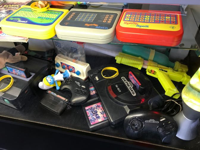 Display case including a Speak and Spell, a super soaker, and a Sega Genesis.