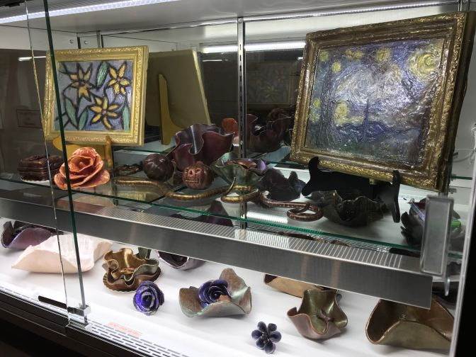 Display case of chocolate decorations, including chocolate paintings, bowls, flowers, and animals.
