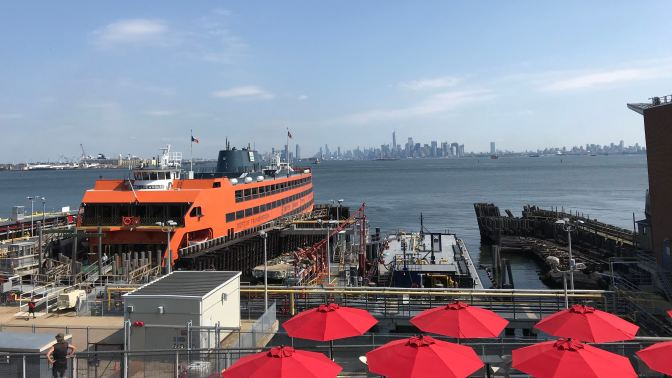 Skyline of New York City in background. The Staten Island Ferry is in the foreground.