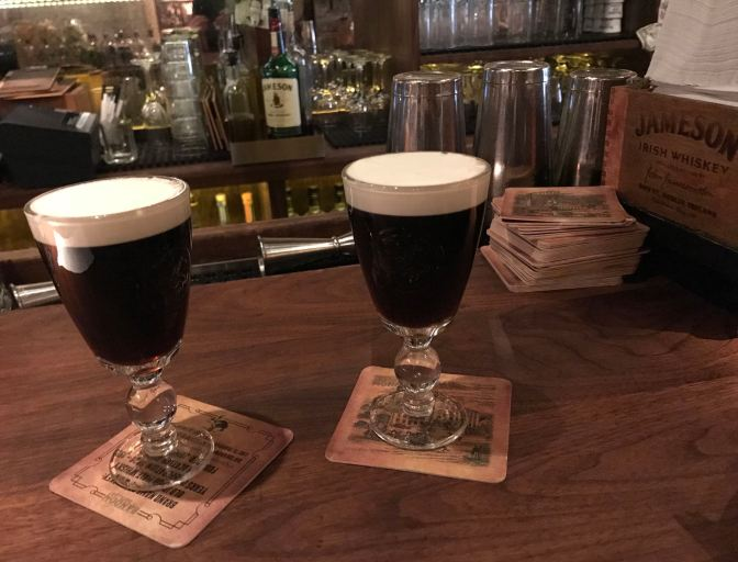Two Irish coffees on the countertop in stemmed glassware.