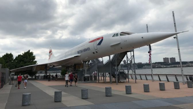 Concorde jet on pier next to hangar.