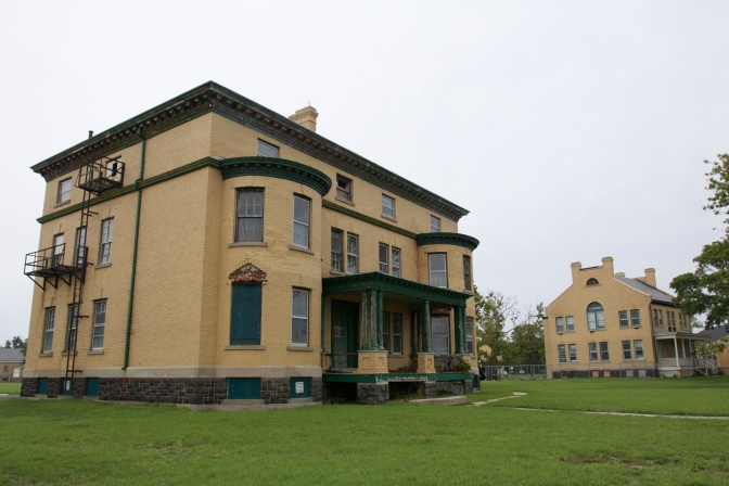 Two large, three story buildings. A large lawn surrounds each one.