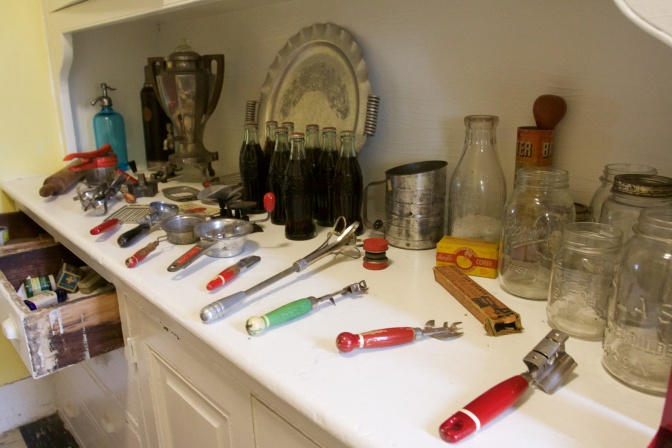 Items on countertop include jars, kitchen implements, and coke bottles.