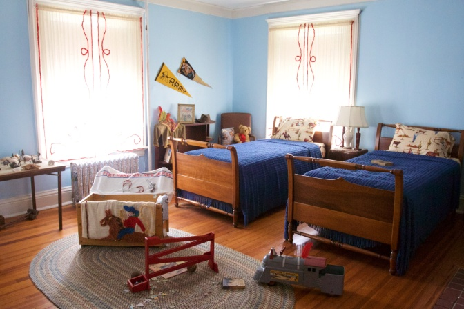 Child's bedroom with two beds. Toys are on the floor.